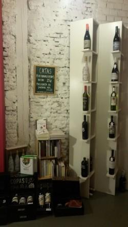 Estantes con botellas de vino y pizarra con precios