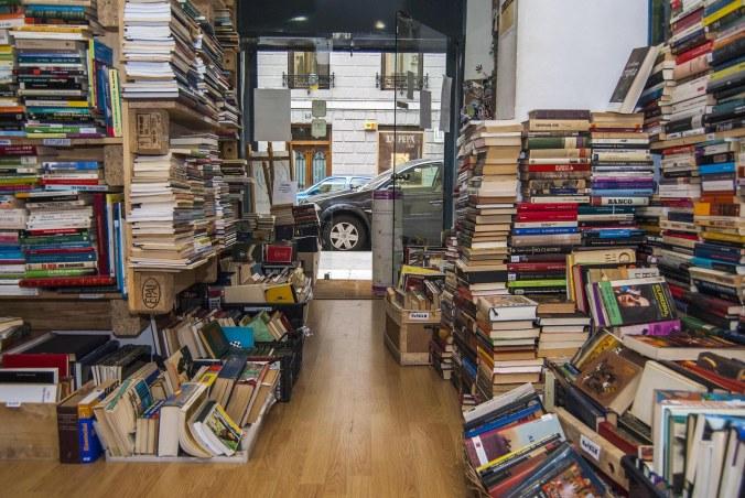 Entrada en la librería con libros en estantes y en el suelo
